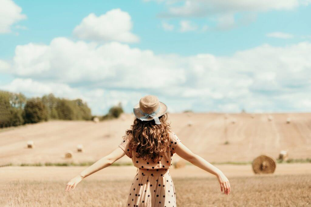 Girl with curly hair, straw hat, polka dot dress lifting her hands up in field. Thanksgiving day